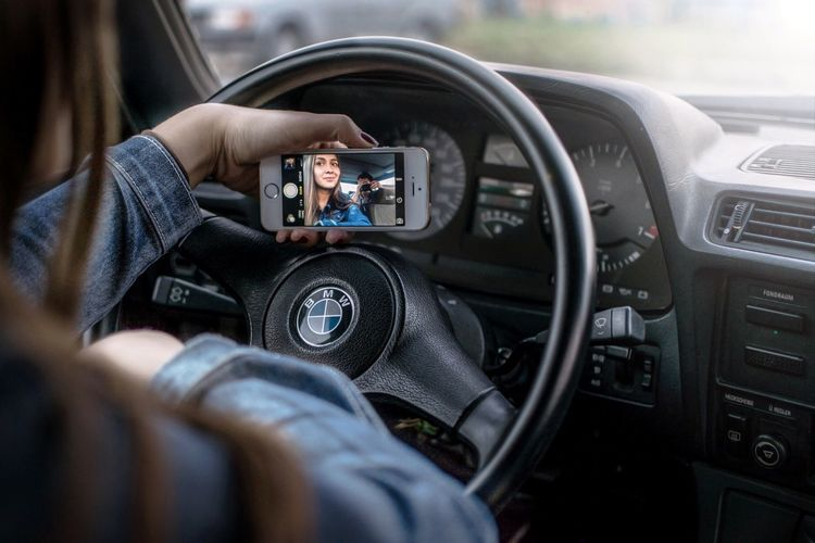 Close-up of man using mobile phone in car