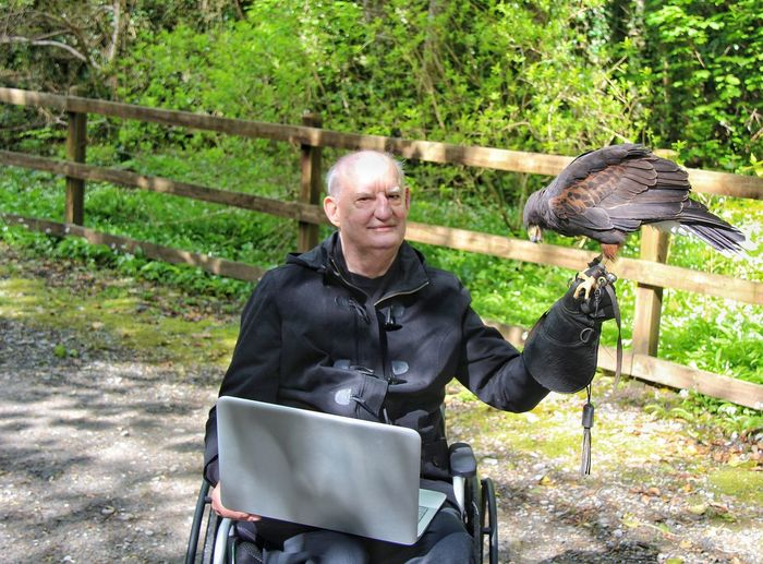 Portrait of man with laptop holding falcon while sitting in park