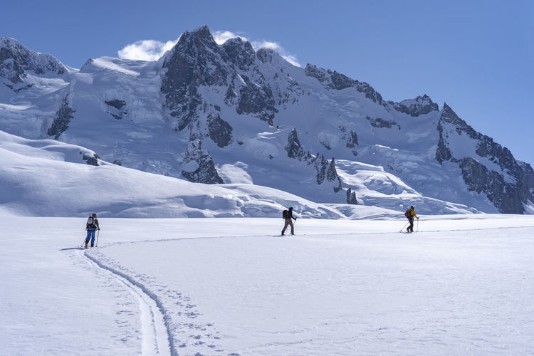 People walking on snow covered mountain against sky