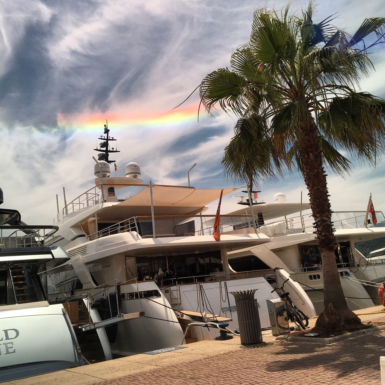 palm tree, tropical climate, sky, tree, water, transportation, nautical vessel, mode of transportation, cloud - sky, nature, sea, plant, moored, outdoors, no people, architecture, built structure, day, travel, sailboat, coconut palm tree, yacht