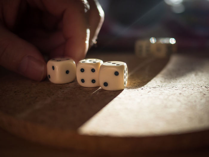 Close-up of hands playing dice on table