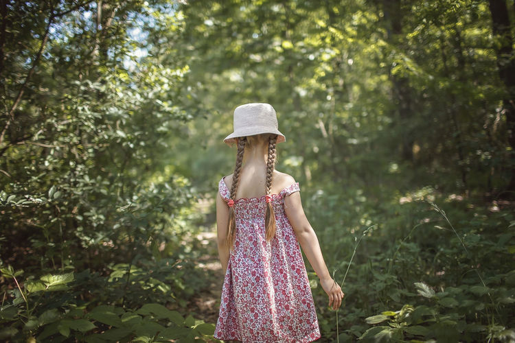Rear view of cute girl wearing hat standing against trees