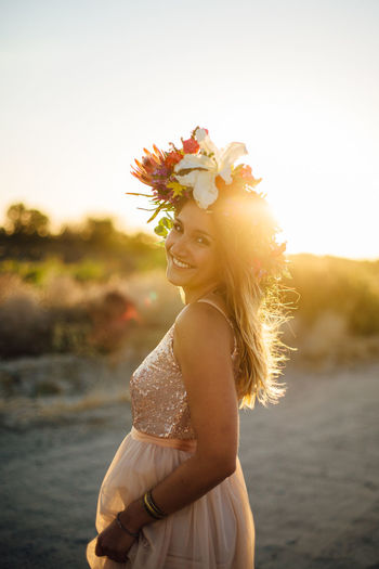 Portrait Of Woman Wearing Flowers Walking At Beach Against Sky