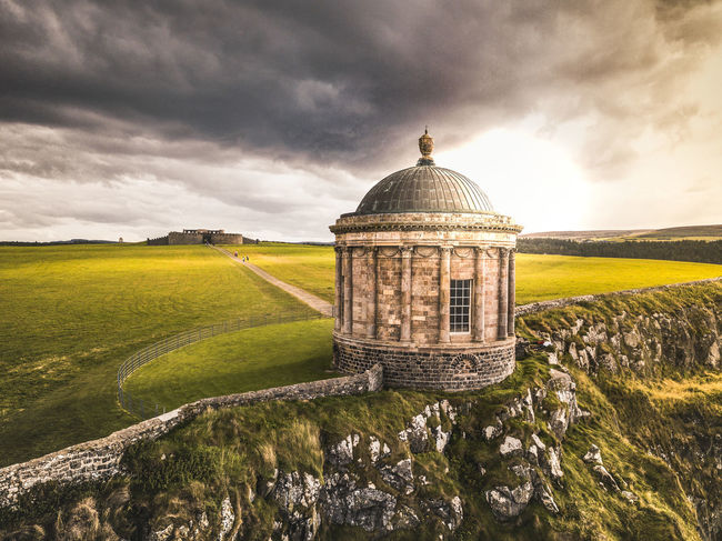 A divine and melancholic fascination Drone  Northern Ireland Travel Photography Agriculture Architecture Beauty In Nature Building Exterior Built Structure Cloud - Sky Dome Dronephotography Environment Grass Land Landscape Mussenden Temple Nature No People Outdoors Plant Scenics - Nature Sky Temple Travel Destinations Autumn Mood