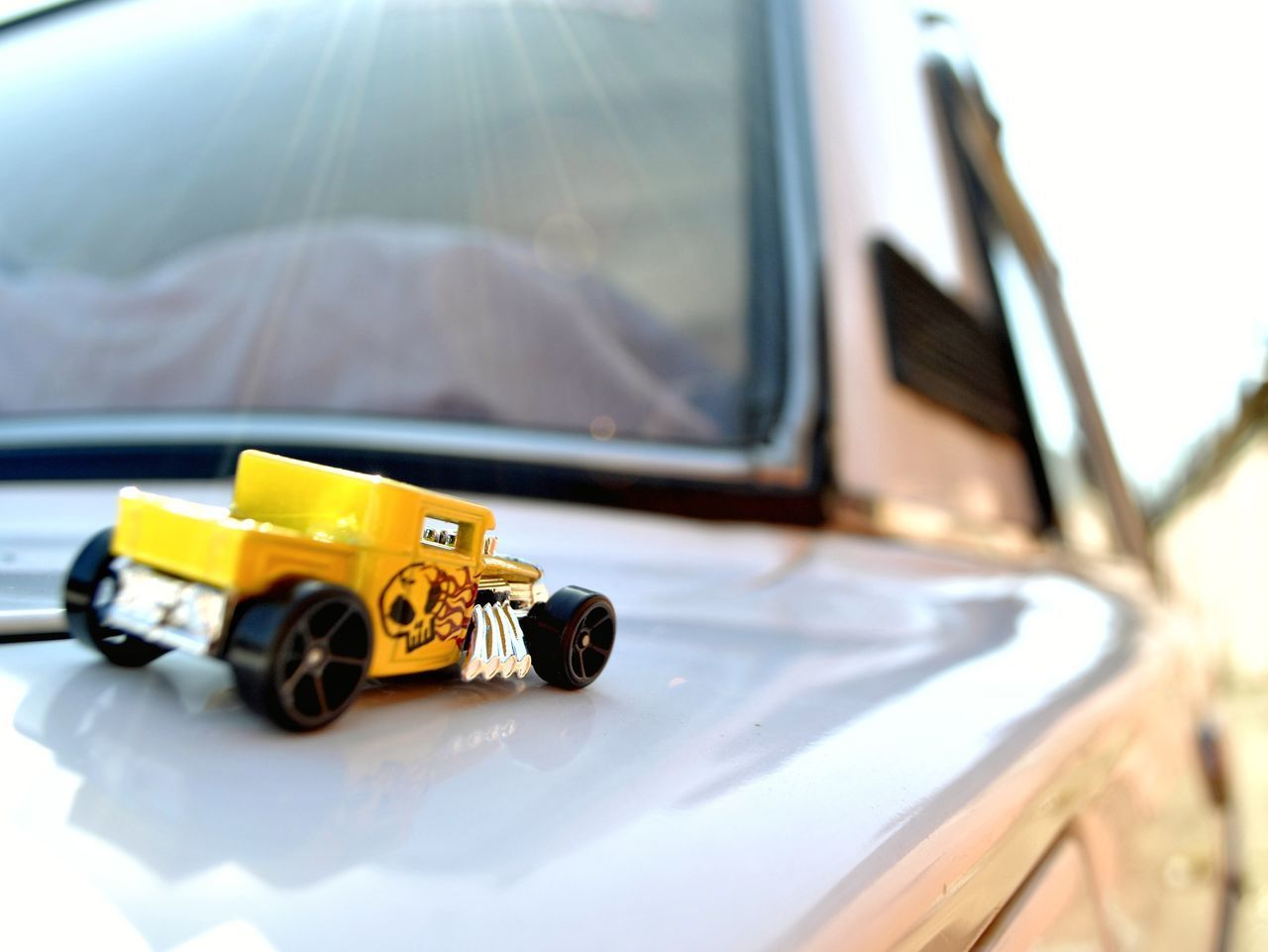 CLOSE-UP OF YELLOW TOY CAR ON BUS MIRROR