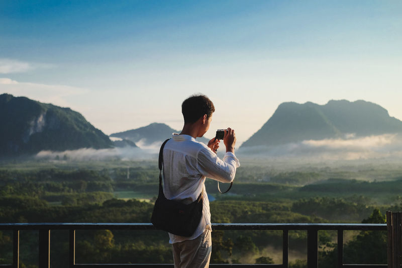 Young Man Photographing Landscape And Mountains Against Sky