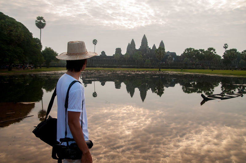 Side view of man looking at angkor wat while standing by lake against sky during sunset