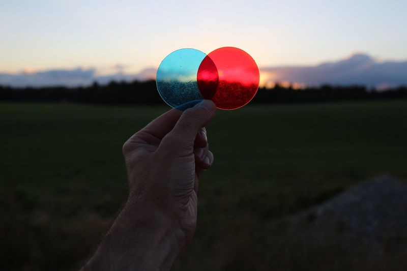 Cropped hand of man holding plastic circles against sky