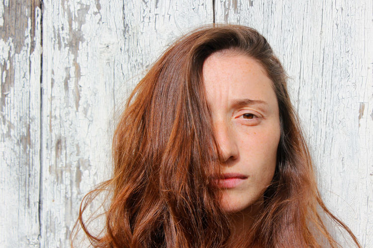 Woman portrait on the wooden background. young beautiful ginger woman. pretty face.