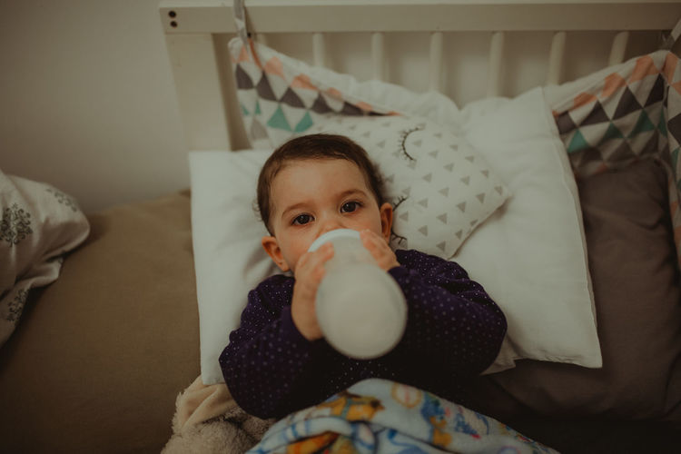High angle portrait of cute boy girl drinking milk while lying on bed