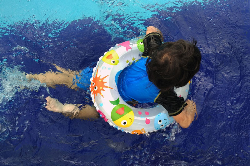 Rear view of boy floating with inflatable ring in swimming pool