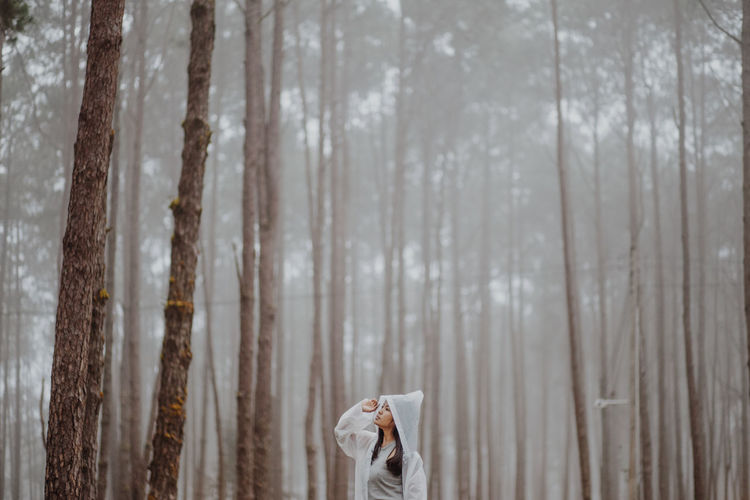 Woman wearing raincoat while standing against trees in forest