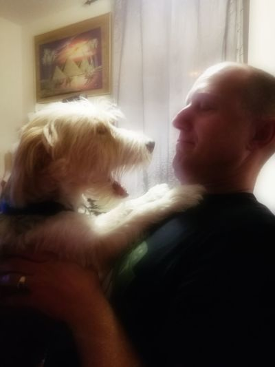 Rear view of man with dog at home