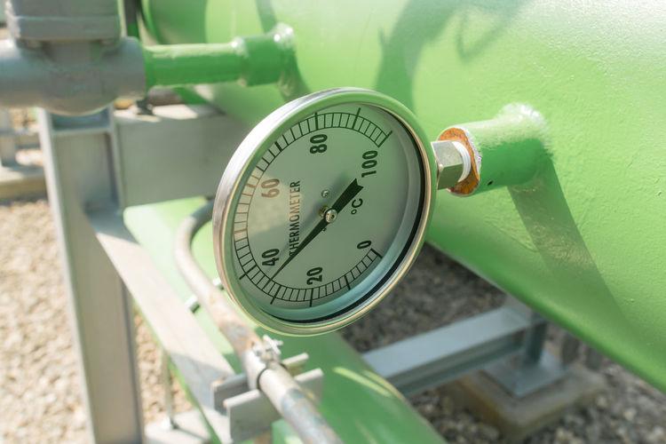 Close-up of gauge on green metallic pipe