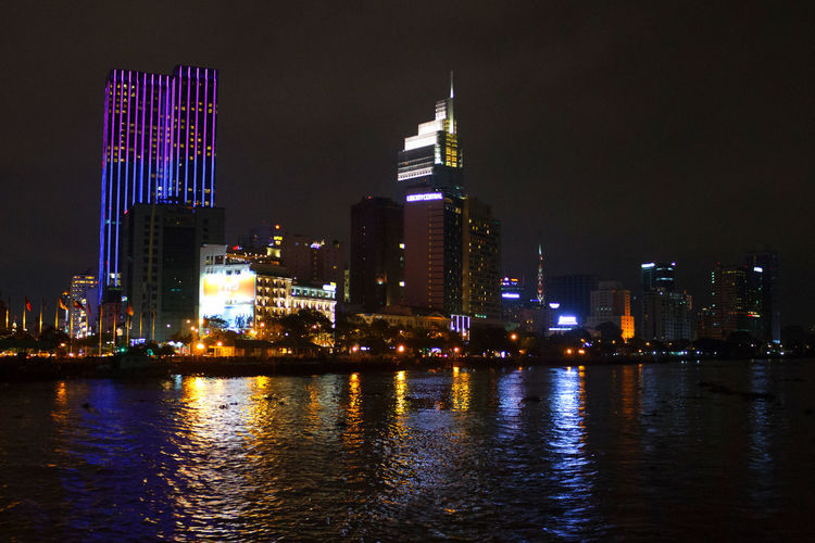Architecture Building Exterior At Night In Vietnam. Nature Vietnam Architecture Building Building Exterior Built Structure City Cityscape Financial District  Illuminated Modern Night No People Office Office Building Exterior Outdoors Reflection River Sky Skyscraper Spire  Tall - High Urban Skyline Water Waterfront
