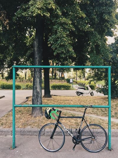 Bicycle parked by railing in park