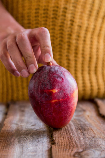 Close-up of hand holding apple on table
