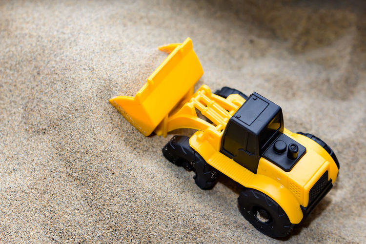 High Angle View Of Toy Bulldozer On Sand