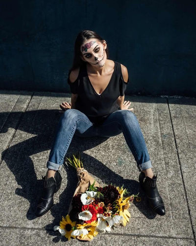 Portrait of woman with spooky halloween make-up sitting by bouquet on footpath