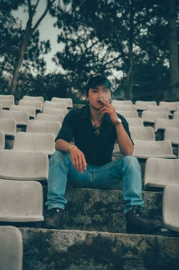Portrait Of Young Man Smoking Cigarette While Sitting On Retaining Wall Amidst Seats