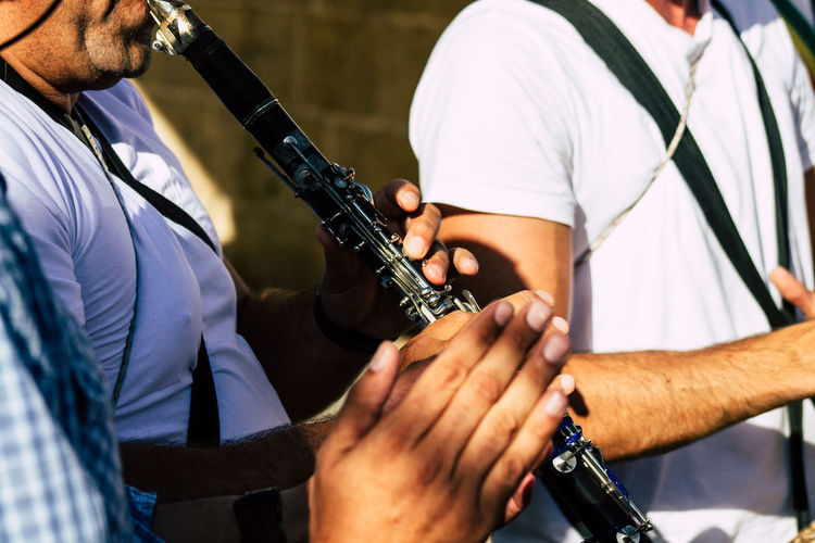 Midsection of people playing saxophone