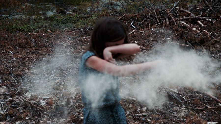 Girl playing with powder on field at forest