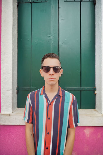 Portrait of man wearing sunglasses standing against wall