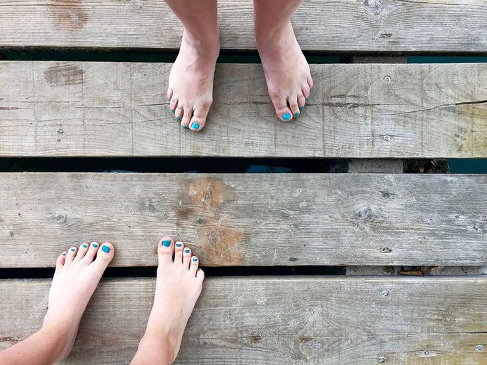 Low section of women with barefoot standing on wooden plank
