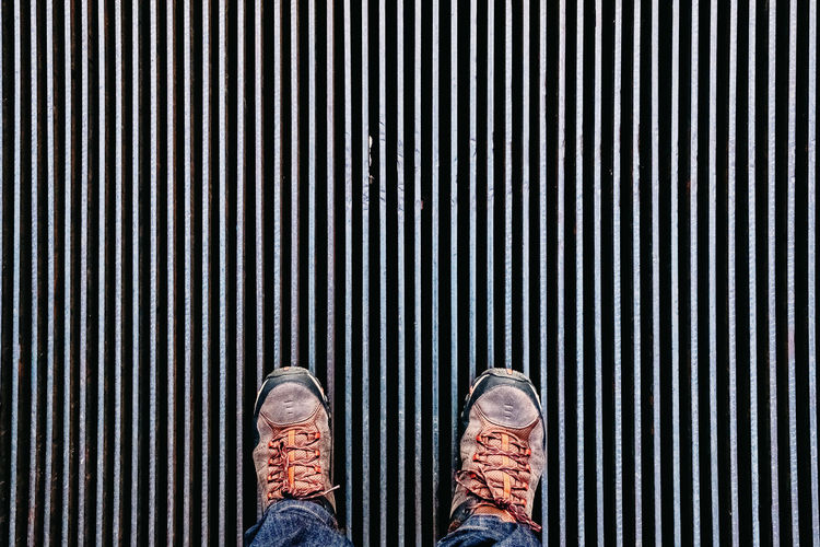 Low section of man standing on metal