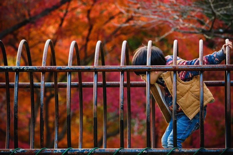 Side View Of Boy Standing In Playground During Autumn