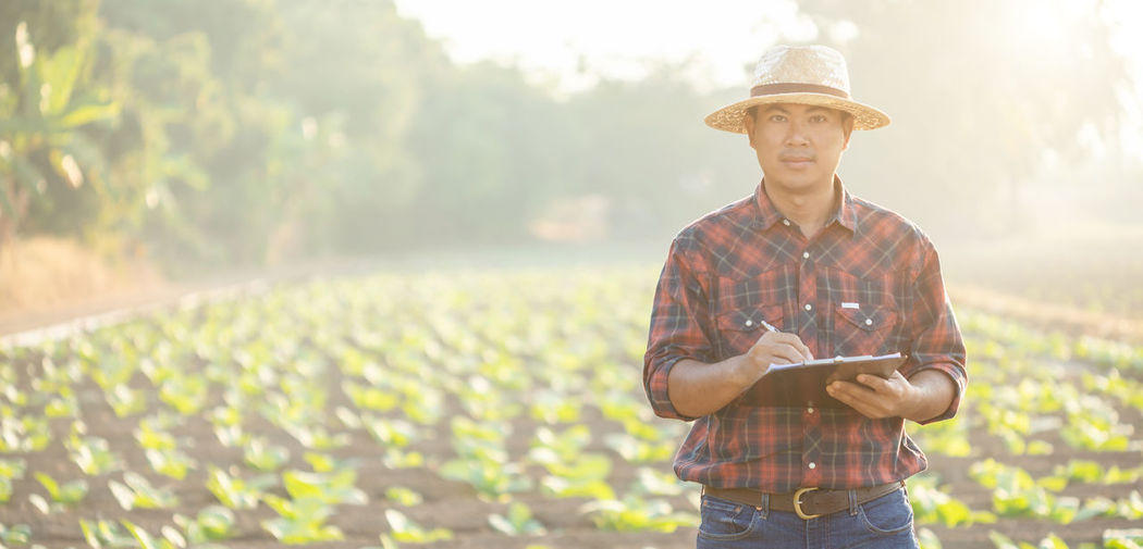 Portrait of man wearing hat standing against plants