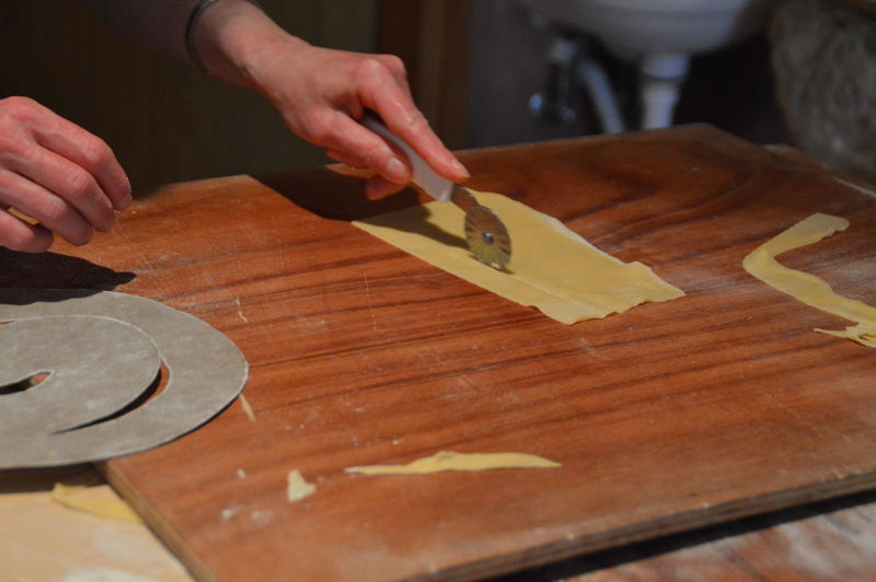 Person Cutting Flat Bread On Wooden Board