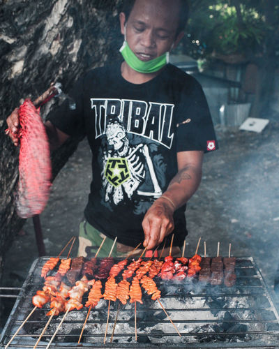 Midsection of man with meat on barbecue grill