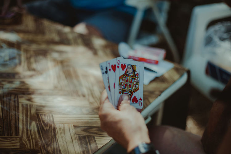 Cropped hand of man playing cards
