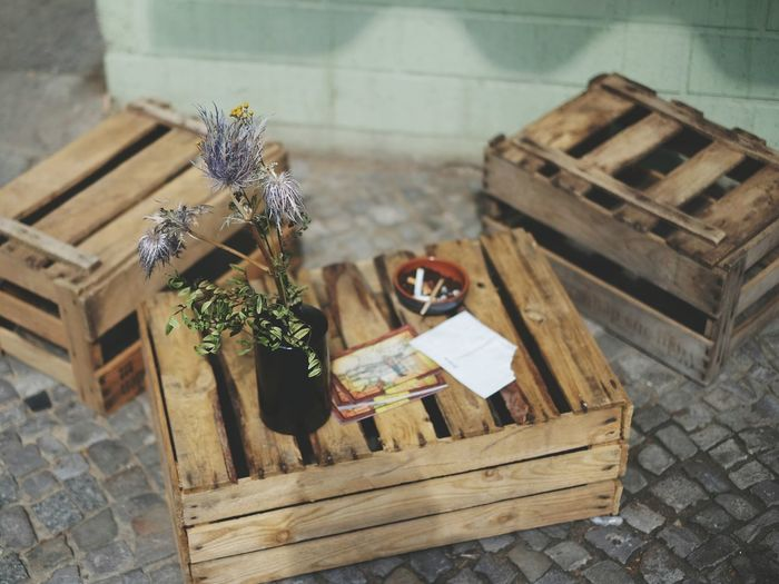 High Angle View Of Potted Plant With Books And Cigarette On Crate