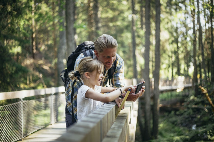 Rear view of girl and woman using mobile phone in forest