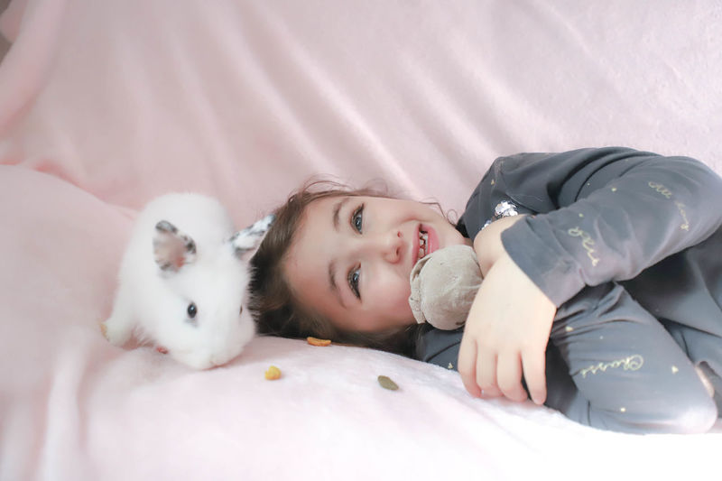 Portrait of smiling girl lying on bed