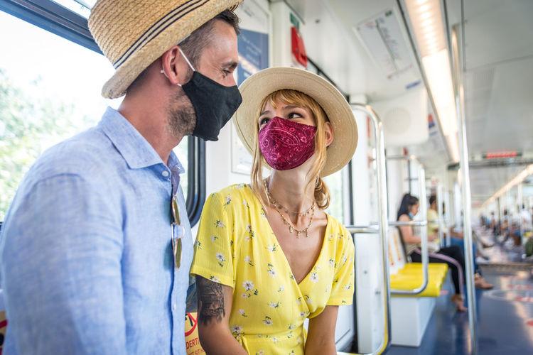 Smiling couple wearing mask sitting in bus