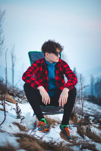 Handsome teenager aged 15-20 in a plaid red-black shirt and sunglasses on a chair by the tent.