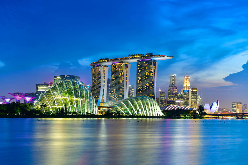 Vibrant color background of Singapore skyline view of skyscrapers on Marina Bay Marina Bay Sands Singapore Architecture Bay Blue Building Building Exterior Built Structure City Cityscape Cloud - Sky Financial District  Illuminated Luxury Modern Night Office Building Exterior Outdoors Sky Skyscraper Tall - High Travel Travel Destinations Water Waterfront