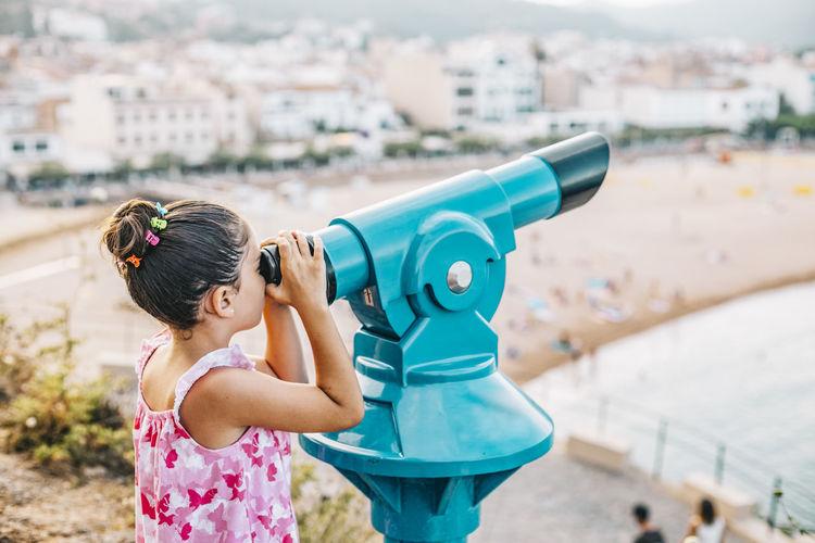 Girl looking the beach through a telescope