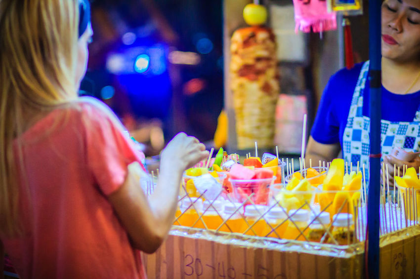 Bangkok, Thailand - March 2, 2017: Unidentified tourist is buying sliced fruits that arranged in plastic cup from street food vendor at Khao San Road night market, Bangkok, Thailand. Khao San Rd Khao San Road KhaoSan Khaosan Rd. Khaosandroad Adult Business Buying Casual Clothing Choice Food Food And Drink Freshness Holding Indoors  Khao San Khao San Knok Wua Khao San Rd. Khaosan Road Khaosanroad Leisure Activity Lifestyles Market Night Market Night Market In Thailand People Real People Retail  Retail Display Selective Focus Standing Store Women
