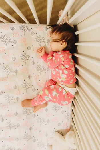 High Angle View Of Girl Sleeping On Bed