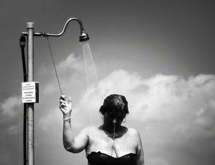 Woman taking shower against sky