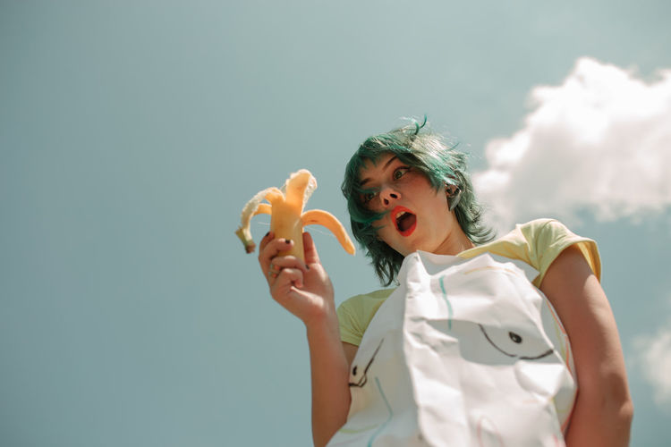Low angle view of woman having banana against sky