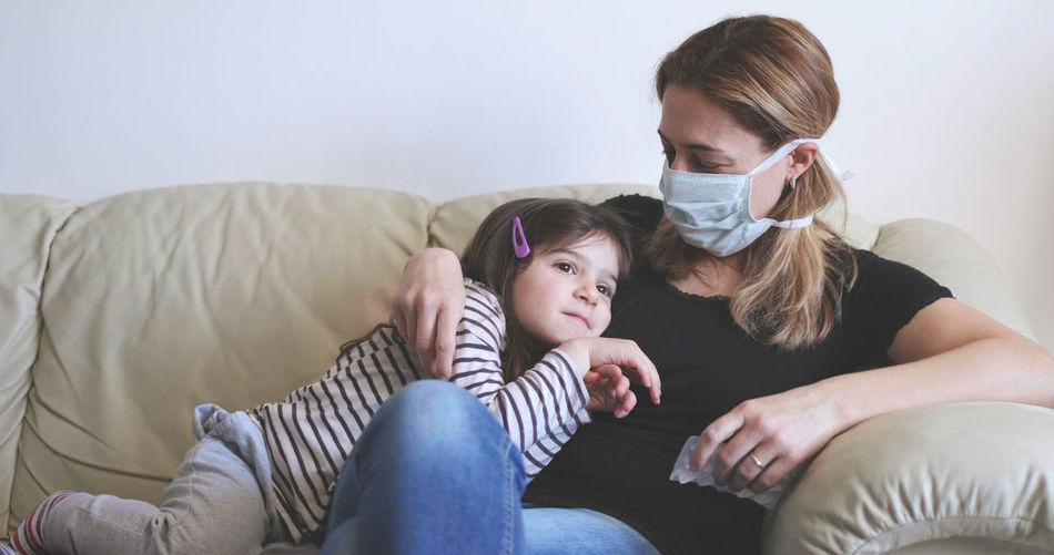 Sick mother with surgical mask stay with her child on the sofa .