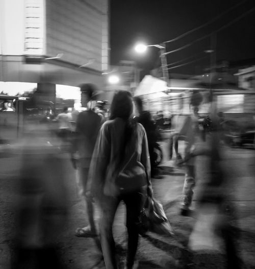 Blurred motion of people walking on road at night