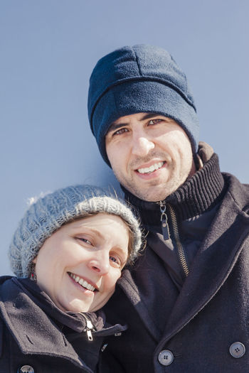 Portrait Of Smiling Mid Adult Couple Standing Against Wall During Winter