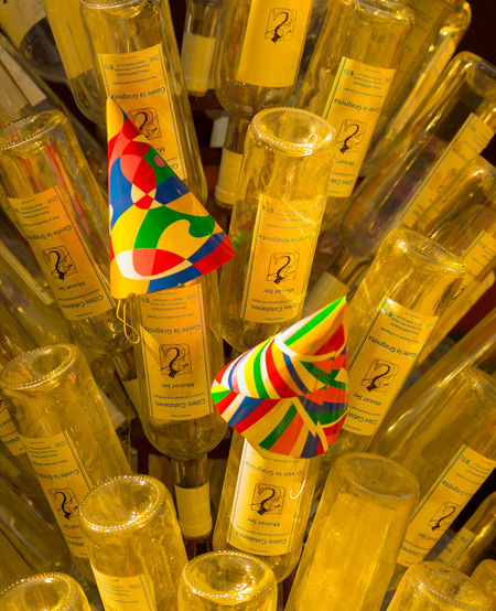 All empty! After The Party Beach Bar Paint The Town Yellow Sunshine On The Bottles Empty Wine Bottles Glass Hanging Large Group Of Objects Multi Colored No People Outdoors Party Hats Retail  Upside Down Wine Bottles On Display