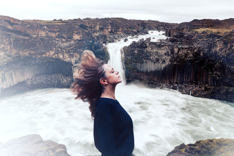 Woman tossing hair while standing against waterfall